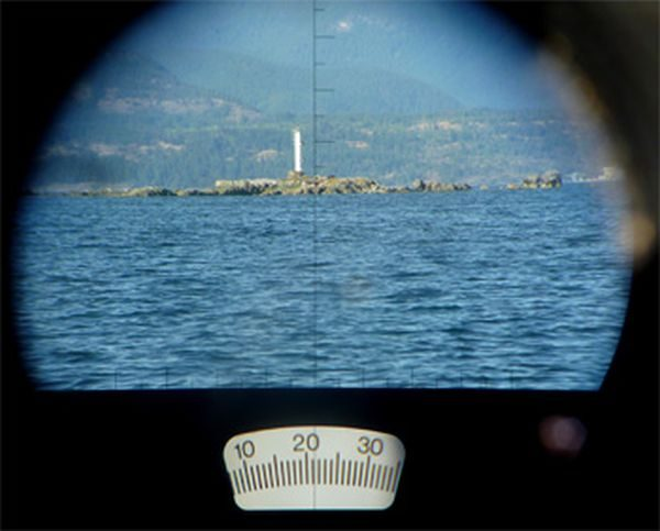 while sailing, taking a bearing using binoculars